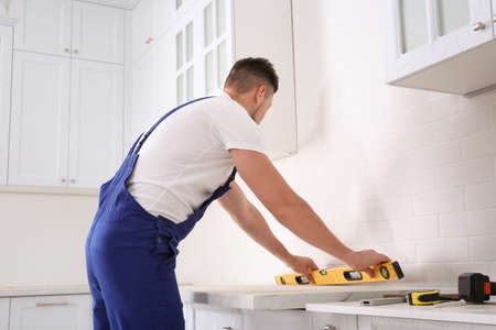 Worker measuring countertop with spirit level in kitchen