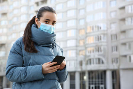 Woman with disposable mask and smartphone outdoors. Dangerous virus