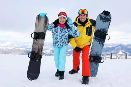 Lovely couple with snowboards on hill. Winter vacation