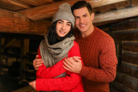 Lovely couple wearing warm sweaters indoors. Winter season