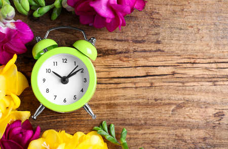Green alarm clock with spring flowers and space for text on wooden table, flat lay. Time change 스톡 콘텐츠