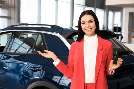 Saleswoman with key near car in dealership Archivio Fotografico