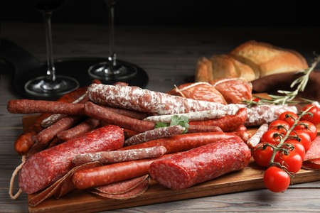 Different tasty sausages on wooden table, closeup