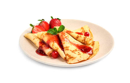 Delicious thin pancakes with strawberries and jam isolated on white