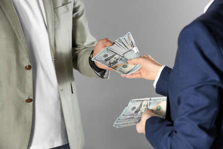 Woman giving bribe money to man on grey background, closeup