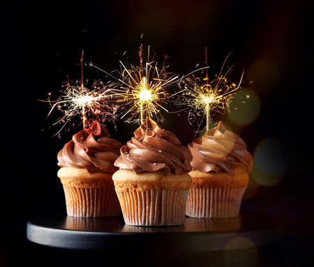 Birthday cupcakes with sparklers on stand against dark background