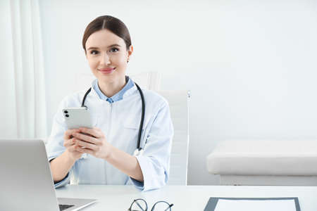 Young female doctor with smartphone at table in office Stock Photo