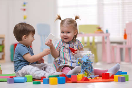 Cute little children playing together on floor at home
