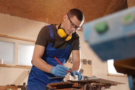 Professional carpenter making mark on wooden bar in workshop