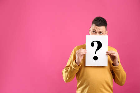 Emotional man holding paper with question mark on pink background, space for text