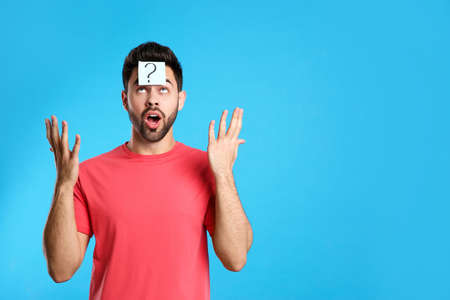 Emotional young man with question mark sticker on forehead against light blue background. Space for text 写真素材