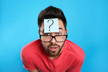 Emotional young man with question mark sticker on forehead against light blue background 写真素材