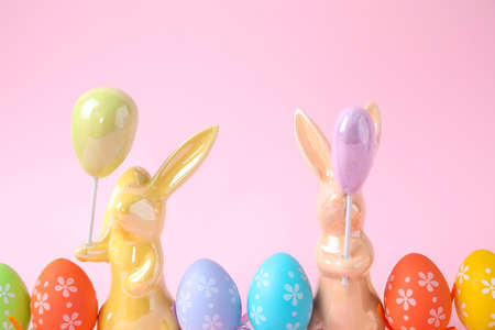 Easter bunnies and painted eggs on pink background