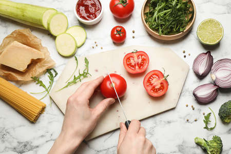 Woman cutting tomato at marble table, top view. Healthy cooking