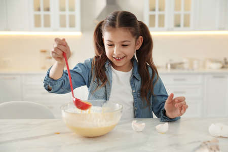 Cute little girl cooking dough at table in kitchen