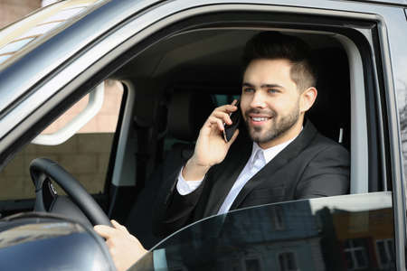 Handsome young man talking on smartphone while driving his car