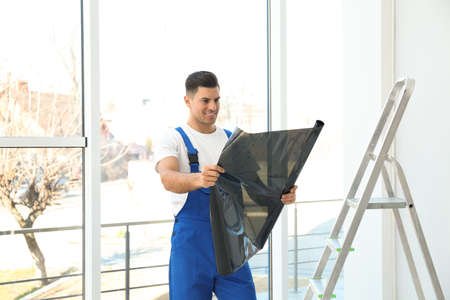 Professional worker with foil indoors. Window tinting Archivio Fotografico