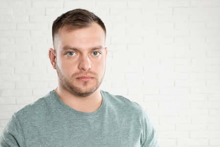 Portrait of young man near white brick wall. Space for text