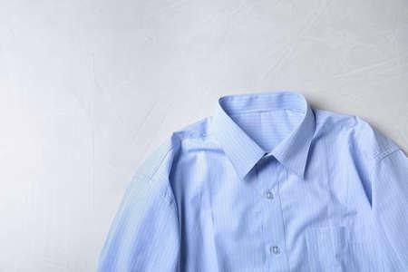 ライトテーブルにスタイリッシュな水色のシャツ、テキスト用のスペースのあるトップビュー。ドライクリーニングサービス 写真素材