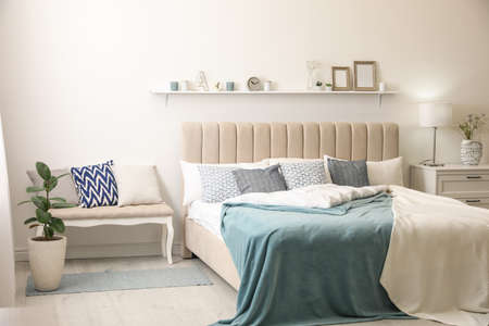 Lit confortable avec oreillers dans la chambre. Design d'intérieur élégant