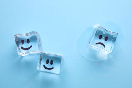 Ice cubes with drawn faces on light blue background, flat lay. Concept of jealousy