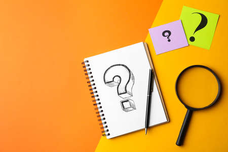 Flat lay composition of notebook, magnifier glass and cards with question marks on color background