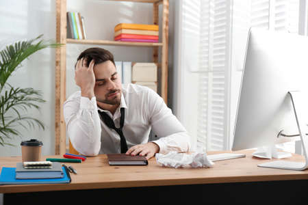 Lazy employee sleeping at table in office
