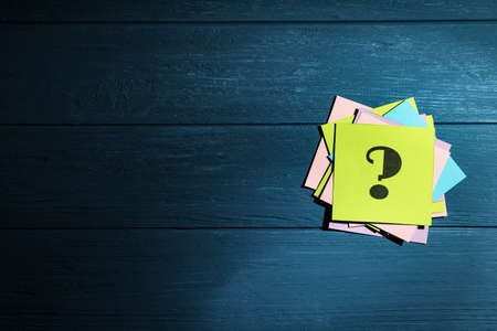Paper cards with question mark on blue wooden background, top view. Space for text