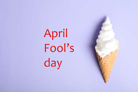 Top view of ice cream cone with shaving foam on violet background, space for text. April Fool's Day