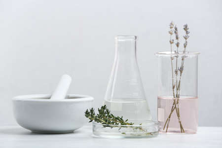 Ingredients for herbal cosmetic products and laboratory glassware on white table Banque d'images