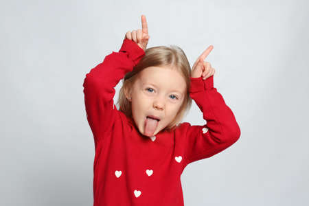 Portrait of cute funny little girl on light grey background