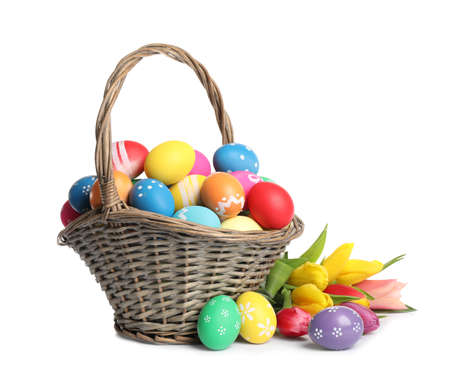 Basket with colorful Easter eggs and tulips isolated on white Archivio Fotografico