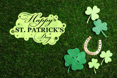 Flat lay composition with horseshoe on green grass. St. Patricks Day celebration