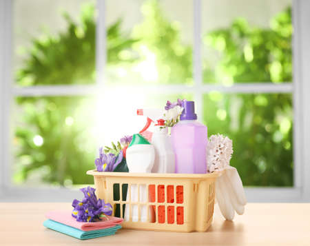 Plastic basket with different detergents on wooden table indoors. Spring cleaning concept