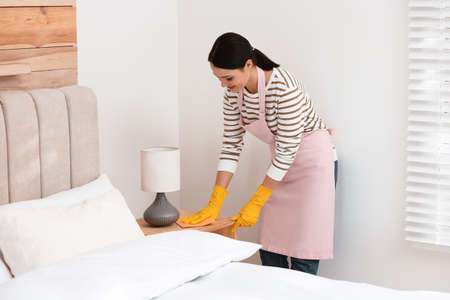 Young chambermaid wiping dust from nightstand in bedroom