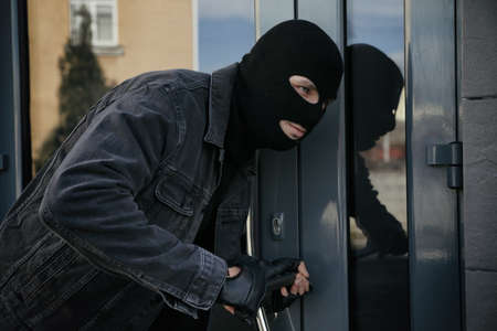 Man in mask forcing door with crow bar. Dangerous criminal