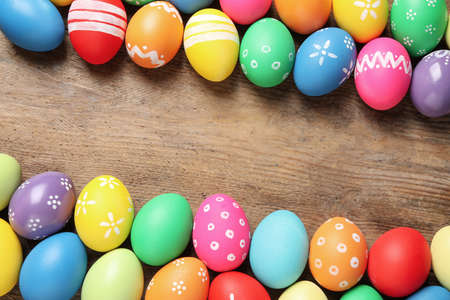 Frame made with colorful Easter eggs on wooden background. Space for text