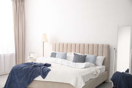 Comfortable bed with pillows in room. Stylish interior design Banque d'images
