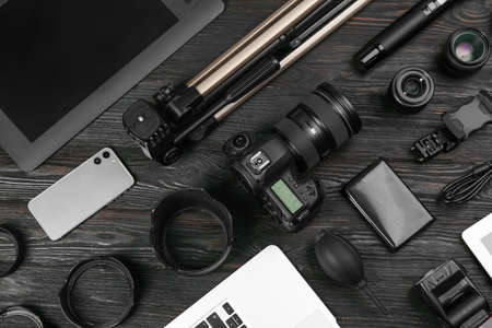 Flat lay composition with camera and video production equipment on black wooden table