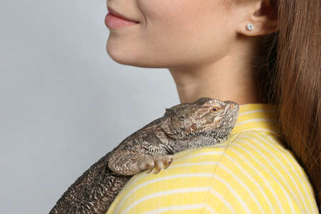 Woman with bearded lizard on grey background, closeup. Exotic pet