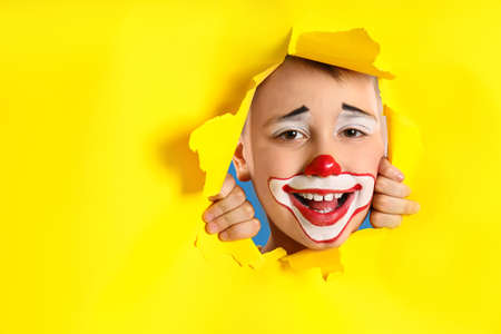 Preteen boy with clown makeup looking out of hole in yellow paper, space for text. April fool's day