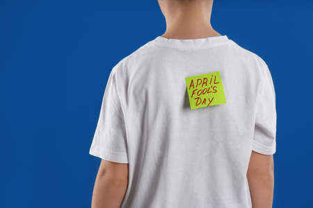 Preteen boy with APRIL FOOL'S DAY sticker on back against blue background, closeup