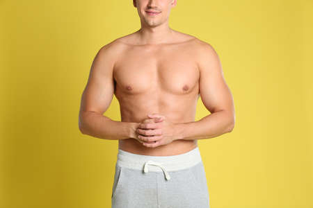Man with sexy body on yellow background, closeup