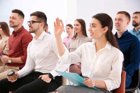 Young woman raising hand to ask question at business training indoors Imagens