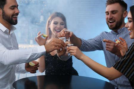 Junge Leute stoßen mit mexikanischen Tequila-Shots am Tisch in der Bar an?