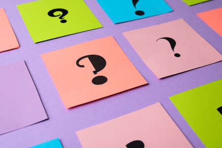 Paper cards with question marks on violet background, closeup