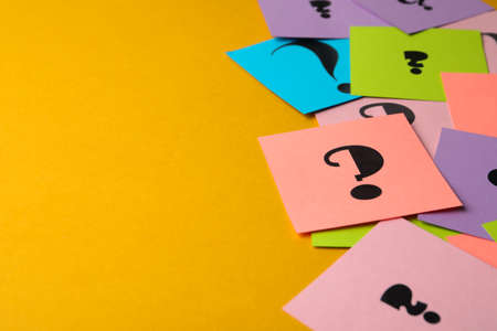 Paper cards with question marks on yellow background, closeup. Space for text