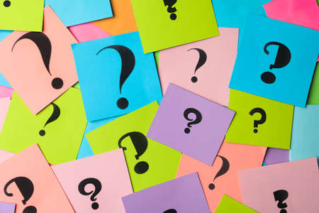 Different colorful paper cards with question marks as background, top view