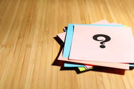 Paper cards with question mark on wooden background, closeup. Space for text