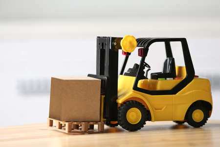 Toy forklift with cardboard box on table against blurred background. Courier service